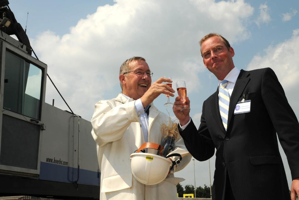 [foto Eut van Berkum: Wethouder Van Gruijthuijsen (links) heft het glas met Rijn & Vecht directeur Rvekamp]