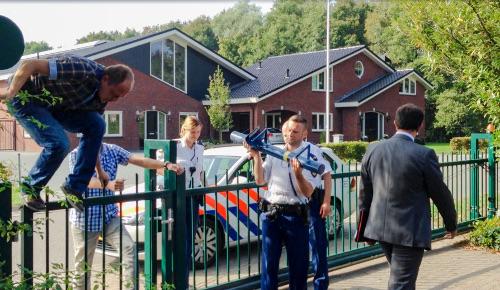 [Fotobijschrift: Agenten zijn zojuist over het hek geklommen, ambtenaren volgen.]